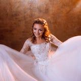 Very happy girl bride in luxurious wedding dress sitting on the floor, portrait in Golden tones. Beautiful girl bride in a luxurious wedding dress, portrait in Royalty Free Stock Photo
