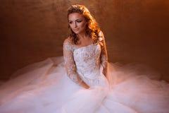 Very happy girl bride in luxurious wedding dress sitting on the floor, portrait in Golden tones. Beautiful girl bride in a luxurious wedding dress, portrait in Stock Image