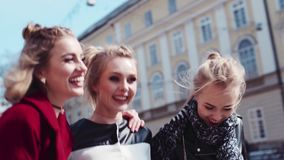 Very happy girls having fun in the city center, hugging and laughing. Leisure time. Time to relax. Friendly atmosphere. Sunny weather. Urban settings on the stock video