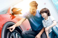 A young family came to the car showroom to choose a new car. They are very happy about this, they are in a good mood. They carefully inspect the car Stock Image