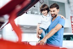 A young family came to the car showroom to choose a new car. They are very happy about this, they are in a good mood. They carefully inspect the car Royalty Free Stock Photos