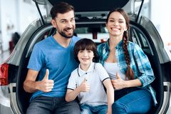 A young family came to the car showroom to choose a new car. They are very happy about this, they are in a good mood. They are sitting in the trunk of the car Royalty Free Stock Image