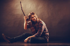 Very happy guitarist and his beloved guitar. Hobby, music concept. Very happy gutarist and his beloved guitar. Man is sitting on the floor and holding the Royalty Free Stock Photo