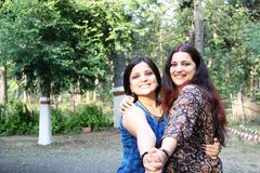 Very Happy Indian (Asian) sisters. In traditional outfit posing with each other on their reunion after an year. joy of meeting each other after a long time stock photo