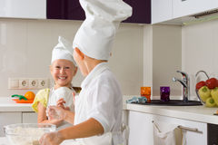 Very Happy Little Chefs Baking in Kitchen. Very Happy Little Chefs Baking Something to Eat in the Kitchen royalty free stock image