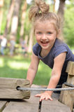 Very happy little girl playing in high wire park Stock Photos