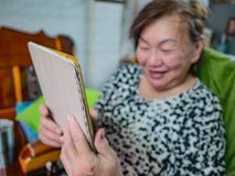 Very happy Old asian women Look at the tablet in her house,Old c stock photography