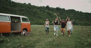Very happy running and jumping group of friends , in the middle of field, beside orange vintage van stock video