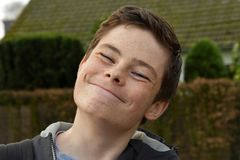 Very happy teenage boy, smirking. Very happy teenage boy grins like a Cheshire cat royalty free stock photos