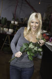 Happy woman holding roses. Very happy woman holding roses in a florist shop royalty free stock images