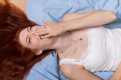 Very Happy Woman Lying on Bed Royalty Free Stock Photography