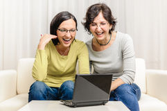 Very happy women chat watching movie home personal computer Royalty Free Stock Photos