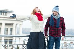 Screaming red hair woman and guy looking to her. Very happy woman crying on the bridge and surprised man. stock image