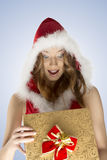 Very happy xmas woman opening gift box. Portrait of happy pretty girl with christmas style, red fur hood and surprised expression opening gift box with red bow Royalty Free Stock Image