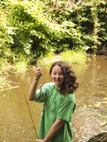 Very happy young girl catches small trout Royalty Free Stock Photo