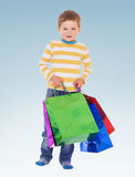 Very heavy bags. With colorful gifts little boy barely carries Stock Photos
