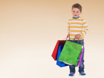 Very heavy bags. With colorful gifts little boy barely carries Royalty Free Stock Image