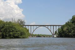 Very high arched bridge over a wide river stock photography