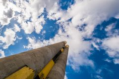 Very high chimney in the Prague housing estate with graffiti. View from the bottom. Blue sky with clouds. An example of socialist or communist architecture royalty free stock photography