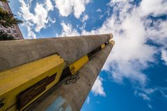 Very high chimney in the Prague housing estate with graffiti. View from the bottom. Blue sky with clouds. An example of socialist or communist architecture royalty free stock photos