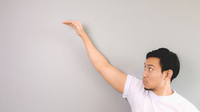 Very high hand sign. An asian man with white t-shirt and grey background stock image