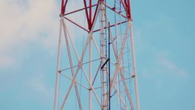 Very high radio tower with transmitting VHF and UHF equipment. Cellular link radio transmitters. Steel tower structure painted in