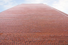 Very high wall of red brick building and cloudy sky Royalty Free Stock Photo