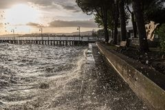 Very high water waves splashing on a lake shore, with drops coming very near to the camera royalty free stock photo