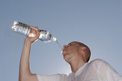 Very hot. Young man with a bottle of water Royalty Free Stock Photo