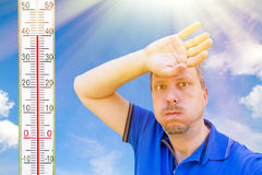 A very hot day in summer. Portrait of a man in the hot sun with thermometer