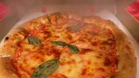 Very hot pizza with smoke. Hand opens a pizza box. Food delivery to your home, business lunch. Camera zooms in on the