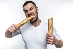 Very hungry man is starving. He broke a long piece of baguette into two pieces. He is eating one of this pieces. He. Looks brutal and weird. Isolated on white stock photography