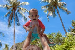Very impressed baby little child raised high in arms against the sky and tropical palm trees. Infant Dressed in a coral and white. Bathing suit royalty free stock photo