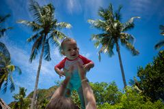 Very impressed baby little child raised high in arms against the sky and tropical palm trees. Infant Dressed in a coral and white. Bathing suit. Smiling girl stock images