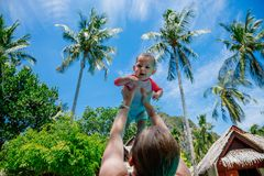 Very impressed baby little child raised high in arms against the sky and tropical palm trees. Infant Dressed in a coral and white. Bathing suit. Happy girl on royalty free stock photos