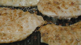 Very juicy and appetizing turkey fillet is prepared in a grill pan. The cook turns over to the other side a chop. Close-up stock video