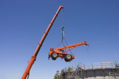 Very large crane lifting small crane. From inside a concrete water tank construction project Stock Photos