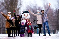 Very large family of three generations: grandmother, father, mother and daughters sculpt big real snowman. Happy family stock photography