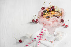 Very large pink milkshake with cherries and chocolate with a pie Stock Image
