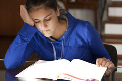 Very listless girl reluctantly studying a textbook. Girlie studying lazy with book Royalty Free Stock Photo