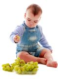 Very little boy eating grapes eat on the floor Royalty Free Stock Images