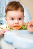 Very little kid eats fresh tasty nutritious curds on highchair Stock Photo