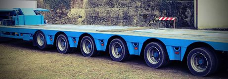 Very long blue truck with six axles of wheels with vintage effe. Very long blue truck with six axles of wheels for exceptional transport with vintage effect stock photo