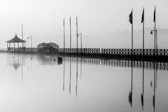 Very long pier in morning fog. Very long wooden pier with lamps and flag poles in morning fog. Very calm water royalty free stock photography