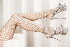 Very long sexy legs in fishnet stockings and extreme platform sh Royalty Free Stock Images