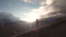 Very long shot Aerial view of an epic shot of a girl walking on the edge of a mountain as a silhouette in a beautiful stock video footage