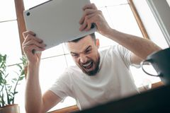 Guy at home. Very mad young man is sitting at the table near the bright window and holding laptop in his hands. He is going to crash the laptop over the table Royalty Free Stock Photos