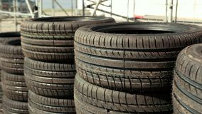 Very many new tires for cars, racing drift, standing on the asphalt stacks. Each other, on the street on a Sunny day, Close up, slow motion stock video