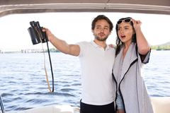 Men with girl lookin for something from yacht stock photos
