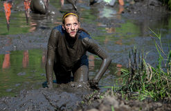 Very muddy girl. Athletes crawl through the thick mud, during the July 2014 mudathlon in northwest Indiana Royalty Free Stock Images